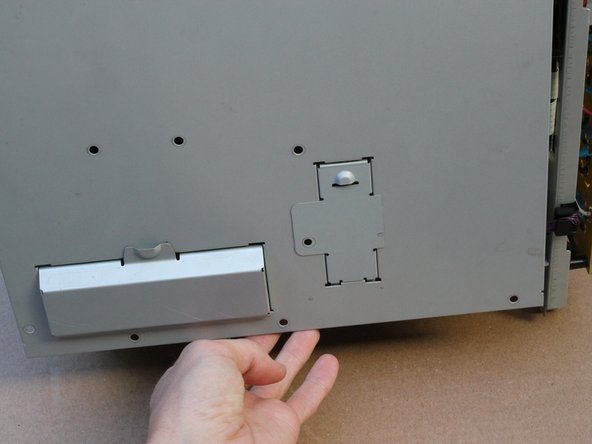 With the screws removed, lift the back cover from the bottom and remove from the printer.