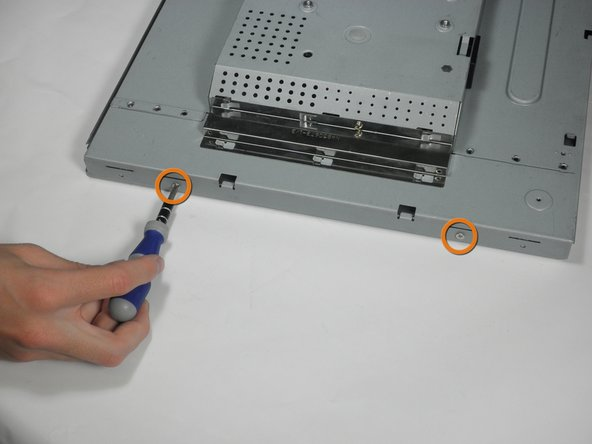 With the monitor still facing down, remove the two 5.81 mm Phillips #2 screws on the left side of the casing.