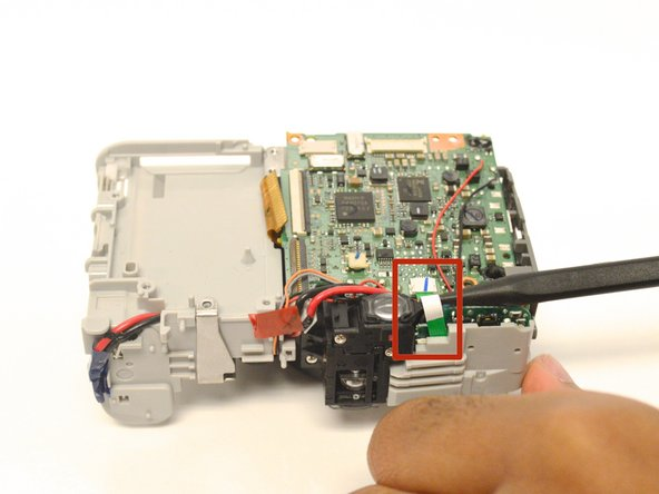 Next, use the spudger to remove the green ribbon from the attached ZIF connector.