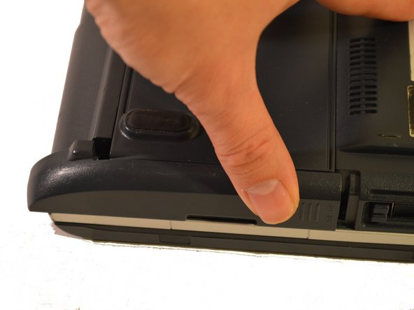 With one finger on the raised grip, slide the latch towards the front of the laptop.