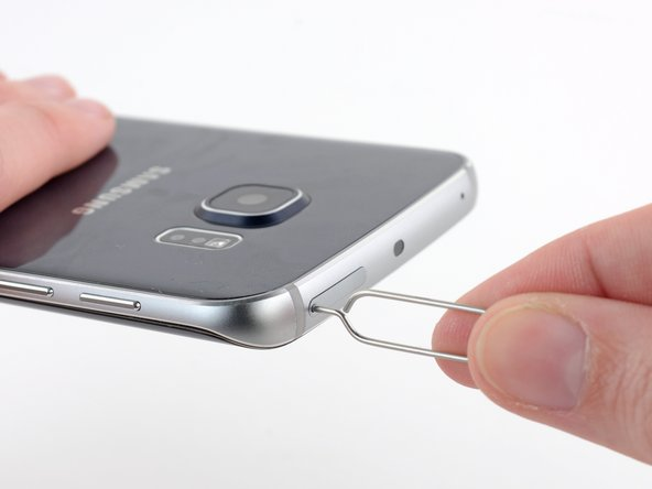 Insert a paper clip or SIM eject tool into the hole in the SIM card slot on the power button side of the phone.