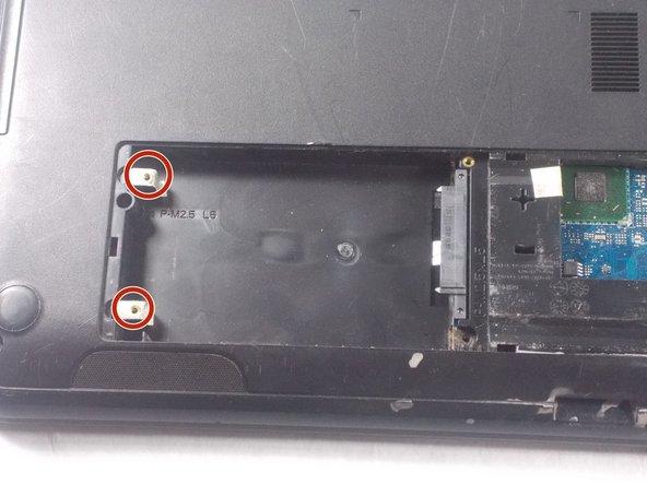 Remove the two 5.5 mm PH1 Phillips head screws holding in the hard drive.