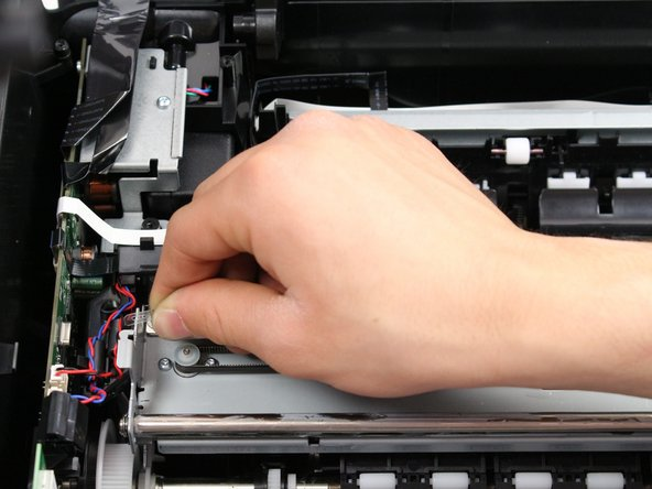Pull the encoder strip  toward the slot it rests on to relieve the tension on the hook and slide the strip off the hook.