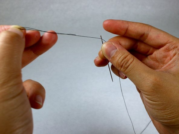 Image 2/3: Match the length of the thread on each side of the loop and cut with the scissors.