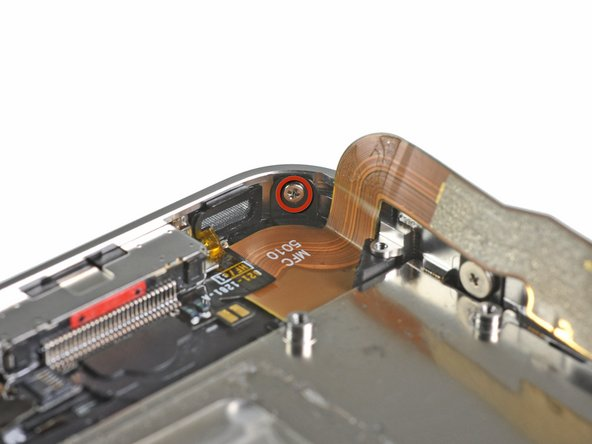 Image 1/1: Remove the 1.6 mm Phillips screw near the dock connector cable.
