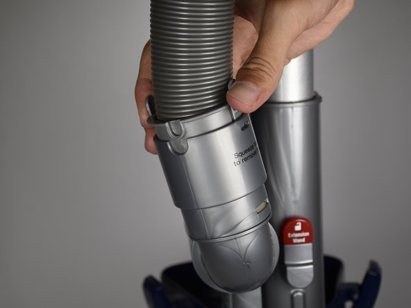 Press on the two grey flaps on either side of the hose simultaneously with your fingers and lift the hose out of the plastic cup with your hand.