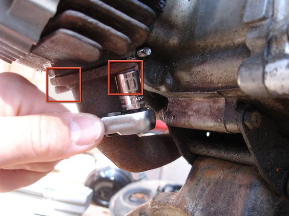 There are two 10 mm hex nuts attaching the muffler to the engine. Make sure you remove both of them before proceeding to the next step.