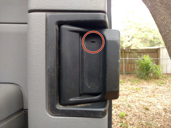 Remove the plastic cover from the door handle using a 7.6 cm slotted screwdriver.