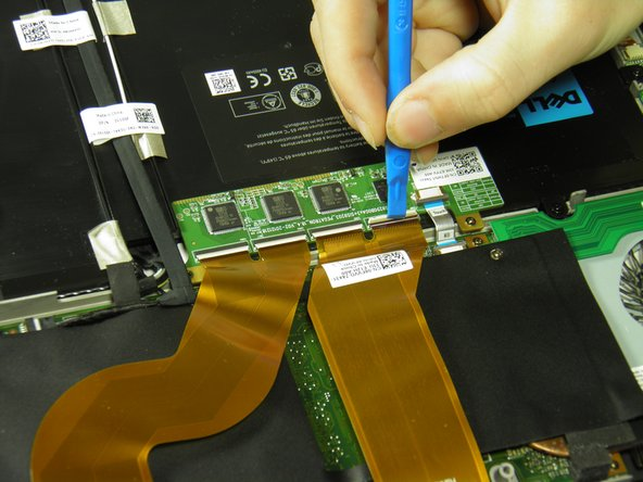 Use the opening tool's angled edge to lift the clasps securing the screen and motherboard cables.