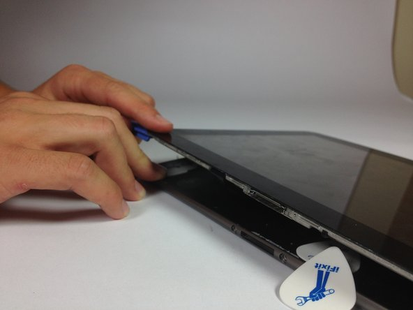 Using the plastic opening tools, continue to carefully run along the right and bottom edge, and then lift the screen from the back panel.
