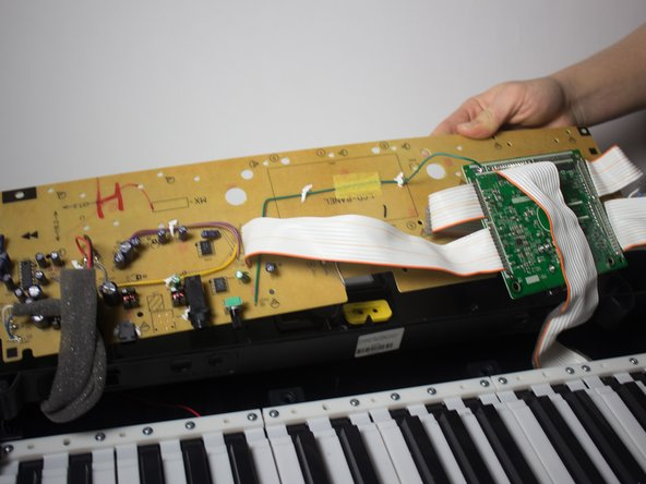 Once all the screws have been removed, lift the panel and place it face down on the keys.