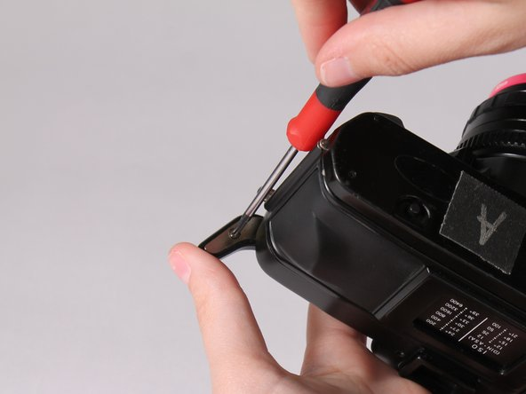 Remove the film advance lever by unscrewing the bottom screw with a Philips screwdriver.