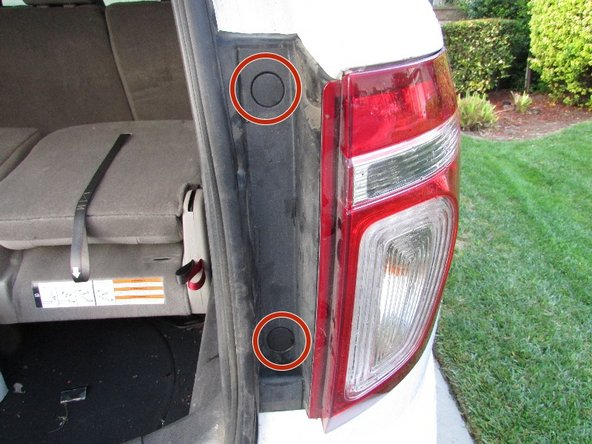 Locate the two plastic screw covers that are adjacent to the rear light covers.