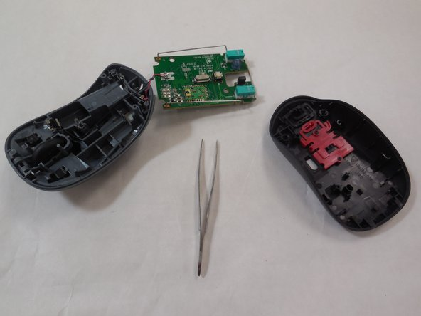 Using the tweezers, gently pull the circuit board from the mouse. Hold the circuit board by the metal frame that surrounds it, as shown.