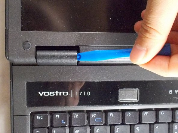 Use the plastic opening tool to loosen the plastic hinge cover that is located above the keyboard.