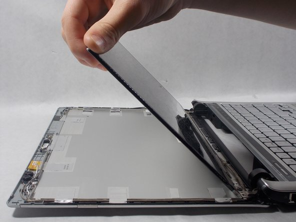 After the screws are out gently flip the screen over onto the keyboard