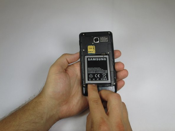 Press your finger into the groove on the bottom left hand side of the battery.