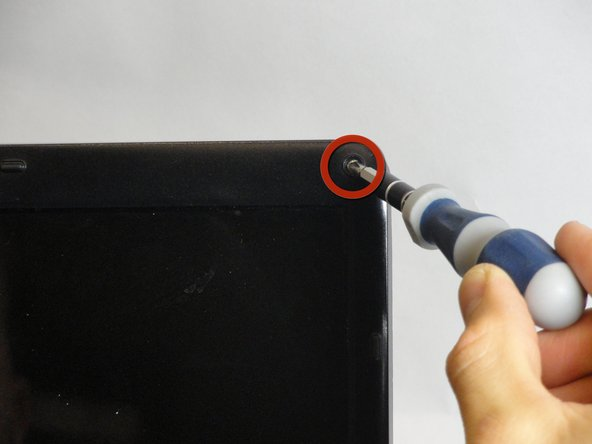 Use a Phillips #00 screwdriver  to remove the four 5.75-mm screws under the plastic covers.