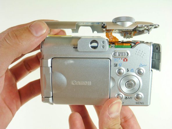Grip the sides of the top cover and gently lift the cover until it detaches from the camera.