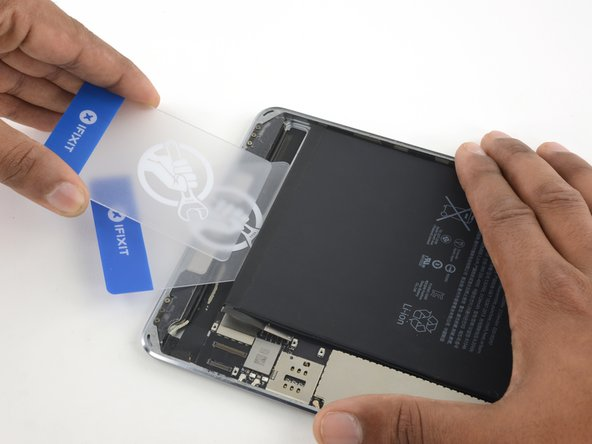Image 1/2: Again, press the card in until about an inch and a half is underneath the battery.