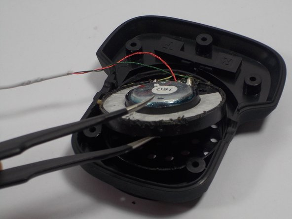 Insert your new speaker into the circular shaped slot located on the speaker cover.