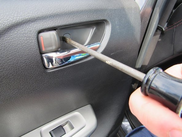 Pry off the plastic tab inside the rear door handle.