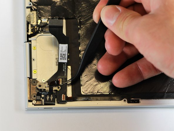 Remove the right charging port by picking it up with the tweezers and lifting it from the computer.