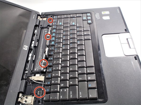 Locate the four 2x2 mm screws that hold the keyboard in place.