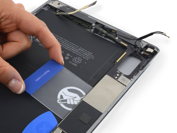 Slide the card down the length of the logic board to release the adhesive.