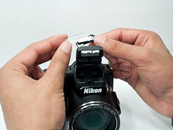 The see-through protective flash covering is stuck on to the flash with thin, double-sided tape. Pull apart the two components to access the flash.