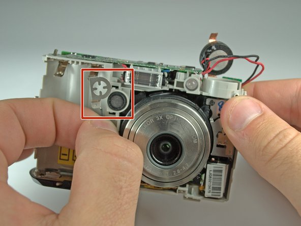 Remove the cross-hair shaped wire cap to the left of the lens.