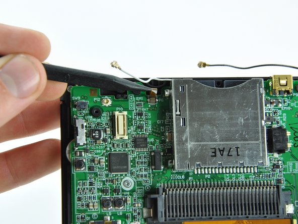 Image 2/2: Use the tip of a spudger to pull the touchscreen ribbon cable straight out of its socket.
