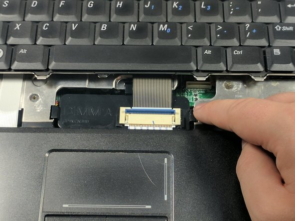 Lift the blue plastic cover so that is at a 90 degree angle to the keyboard to remove the connection to the keyboard.