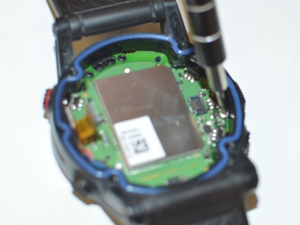 Use your Torx T9 screwdriver to remove the one  .8mm screw that holds the main board to the watch housing.