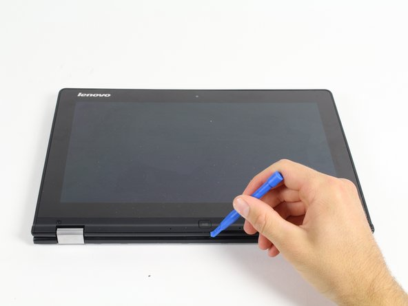 Image 1/2: Using a plastic opening tool, carefully remove the small plastic piece at the bottom of the screen.