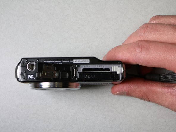 "On the bottom of the camera, move the gray switch that has the words ""open"" and ""lock"" above it to the open position. The case will open."