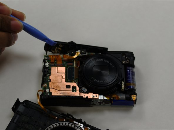 Carefully lift the top panel off the camera using a prying tool.