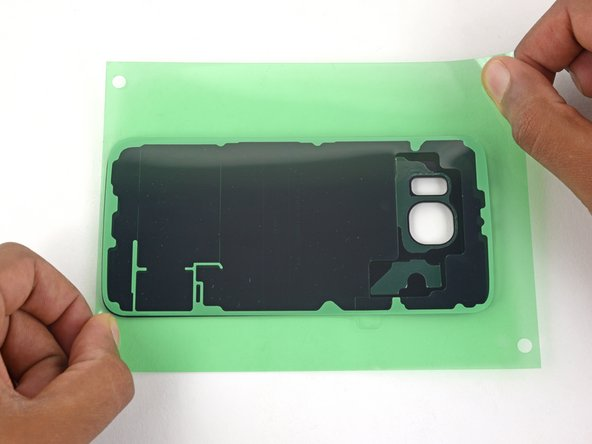 Lay the glass panel face-up and rotate it so that the lens holes are on your right.