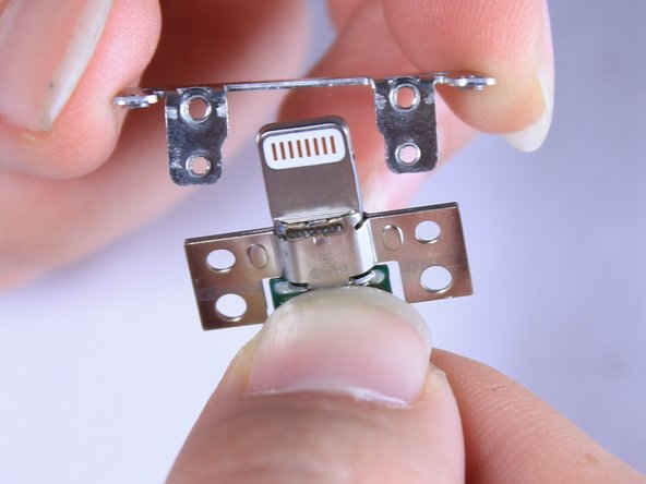 Remove the metal frame from around the lightning connector. This will allow you to replace the lightning connector with a new one.