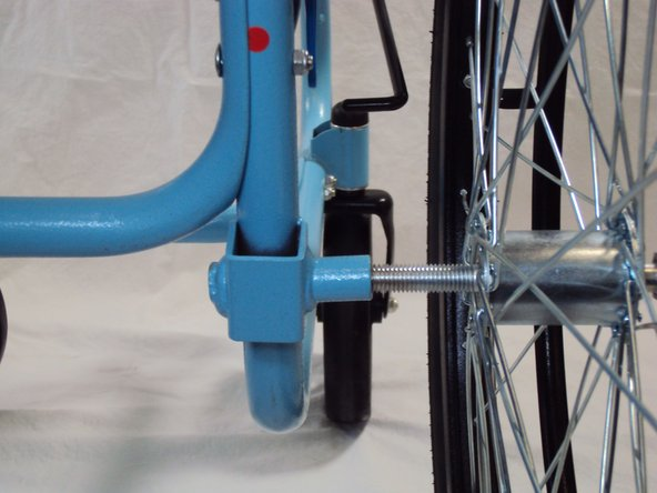 Image 2/2: Insert the wheel with the axle bolt into the lower back of the frame.