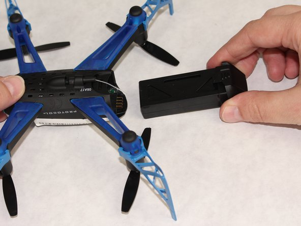 Slide the battery pack out of the drone. When replacing be mindful of the antenna as it is easily crushed.