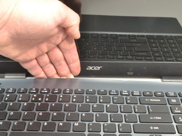 Put your fingers under the top of the keyboard assembly directly below the Acer logo.