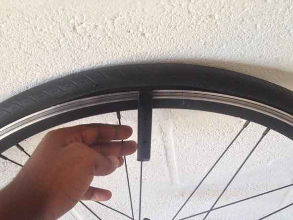 Insert the flat end of the tire lever between the inside wall of the tire and the outside of the rim.