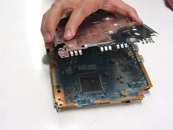 Gently lift the metal plates from the top and the bottom of the motherboard.