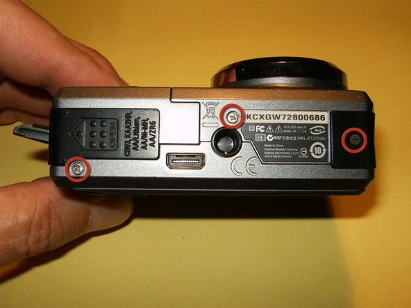 Remove the three screws on the bottom of the camera, where the battery hatch is located.