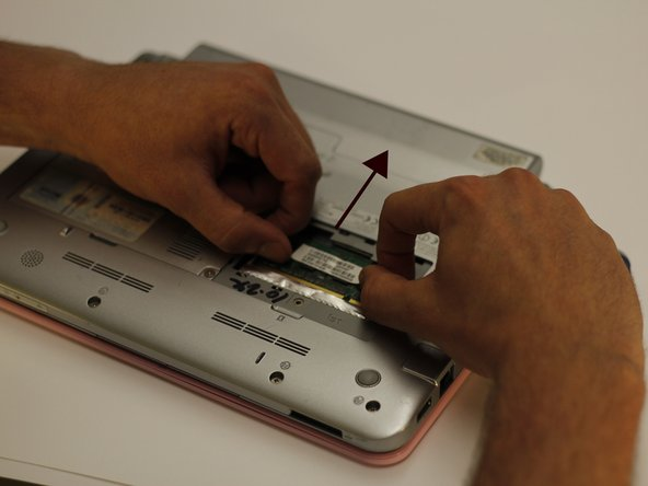 After the retainer arms are free, push the chip towards the top of the netbook. This will free the chip for removal.