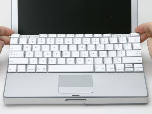 Image 1/1: Lift the keyboard by the 'esc' and 'eject' keys and gently lift up until the keyboard is vertical.