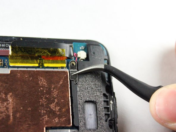 Image 1/1: Use your tweezers to take off the small metal retaining bracket on the bottom right of the phone.