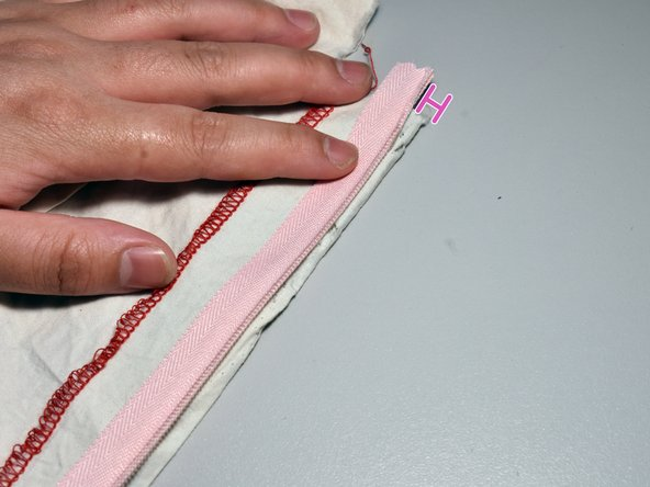 Place the replacement invisible zipper on the table, with the teeth side pointing up and the zipper pull facing down.