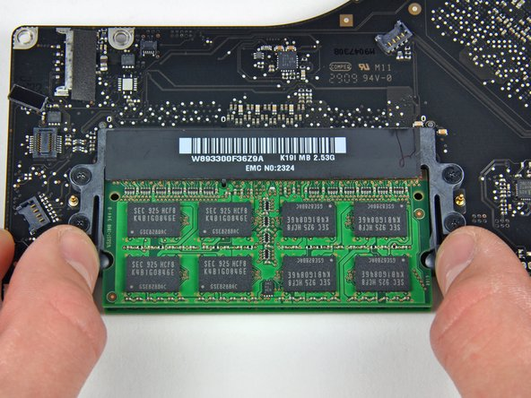 Image 1/2: Release the tabs on each side of the RAM chip by simultaneously pushing each tab away from the chip.